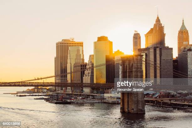 Sunset over Brooklyn Bridge and skyline of Manhattan Financial District in Downtown, New York City, NY, United States