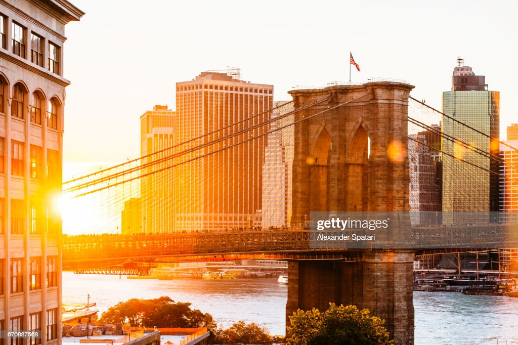Sunset over Brooklyn Bridge and skyline of Manhattan Financial District in Downtown, New York City, NY, United States : Foto de stock