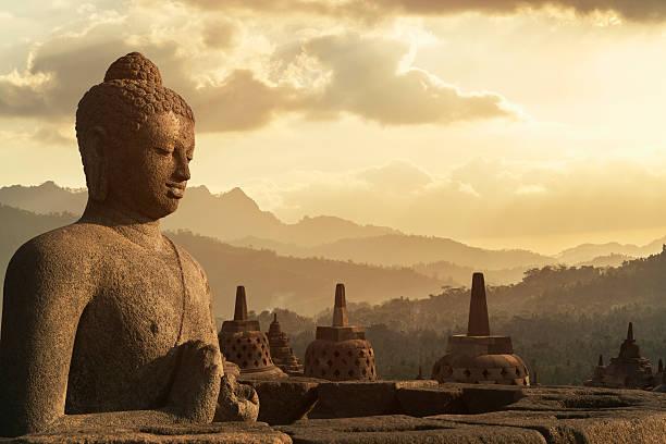 Sunset over Buddha statue in Borobudur.