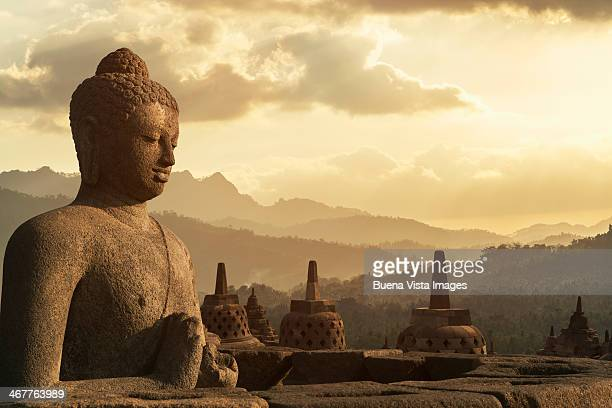 Sunset over Buddha statue in Borobudur.