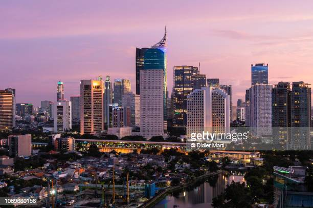 sunset over business district jakarta skyline - jakarta stock pictures, royalty-free photos & images