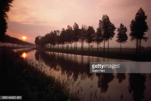 sunset over canal - damme stock pictures, royalty-free photos & images
