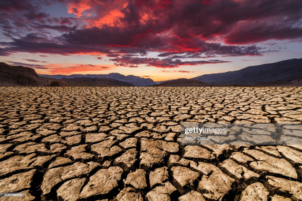 Sunset over cracked soil in the desert. Global warming : Stock Photo