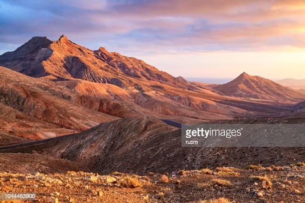 pôr do sol sobre a paisagem do deserto de fuerteventura, ilhas canárias - marrom - fotografias e filmes do acervo