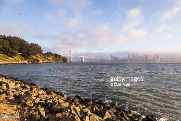 sunset over downtown san francisco, the oakland bay bridge from treasure island - treasure island california stock pictures, royalty-free photos & images