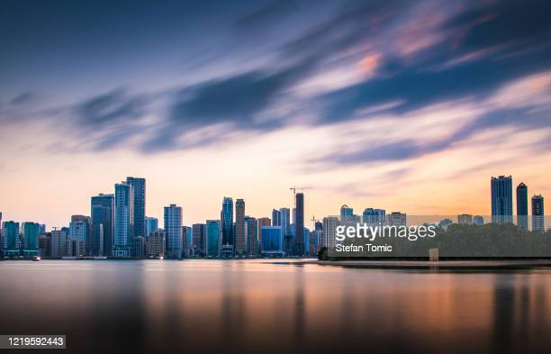 sunset over emirate of sharjah skyline - emirate of sharjah stock pictures, royalty-free photos & images