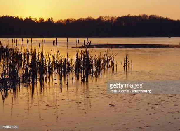 Sunset over frozen Frensham Pond, Frensham, Surrey England, UK