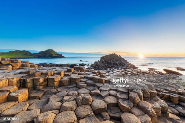 sunset over giants causeway, northern ireland - coastline stock photos and pictures