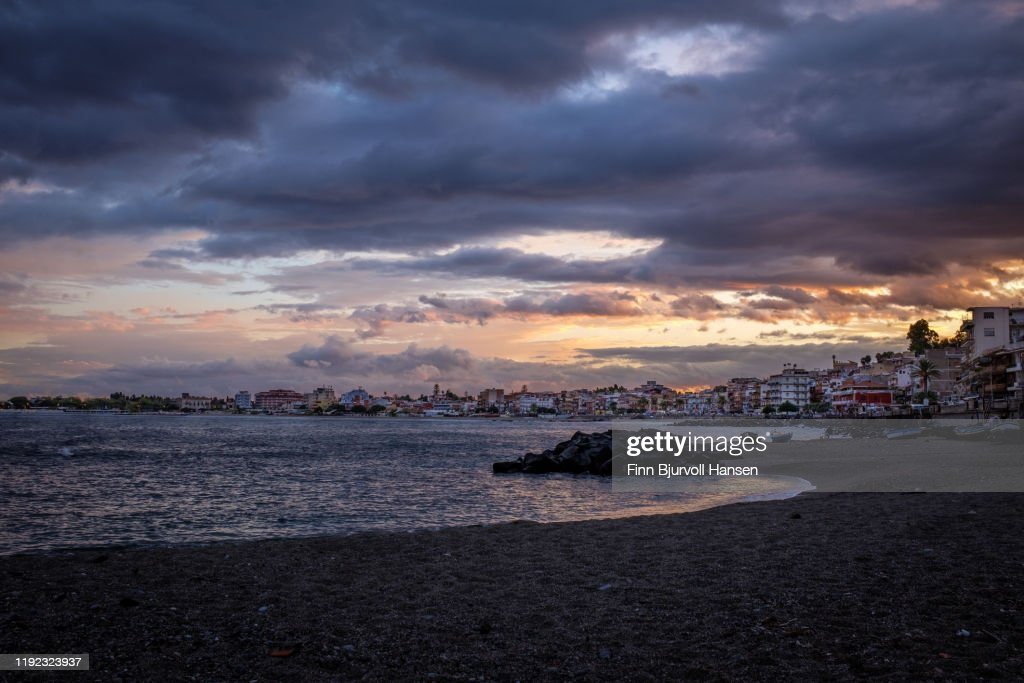 Sunset over Giardini Naxos, Ocean to the left, city to the right : Stock Photo