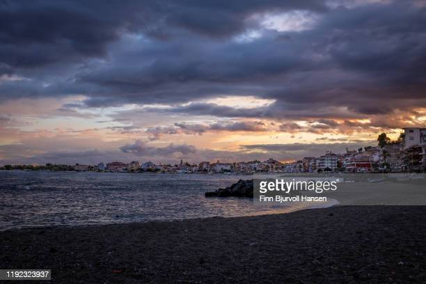 sunset over giardini naxos, ocean to the left, city to the right - finn bjurvoll stock pictures, royalty-free photos & images