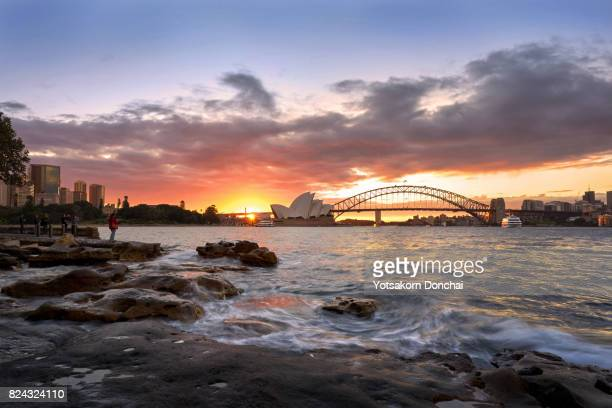 A sunset over Harbour Bridge and Sydney Opera House from Mrs. Macquarie's Point, Australia