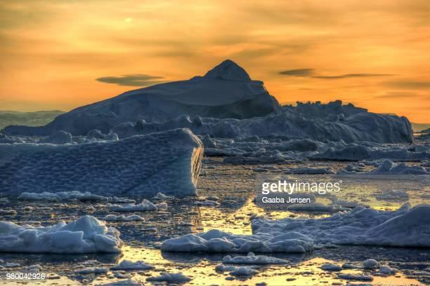 sunset over icebergs in water, ilulissat, qaasuitsup, greenland, denmark - ilulissat stock-fotos und bilder