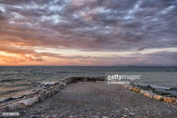 sunset over izmir bay with a man standing near the sea in spring. - emreturanphoto stock pictures, royalty-free photos & images