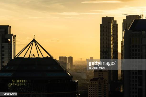 sunset over jakarta business district in indonesia capital city. - emerging markets stock photos and pictures