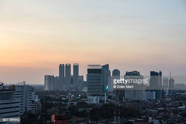 sunset over jakarta skyline - didier marti stock photos and pictures