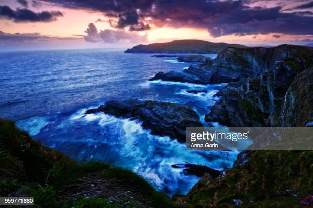 Sunset over Kerry Cliffs along Skellig Ring, long exposure on surf