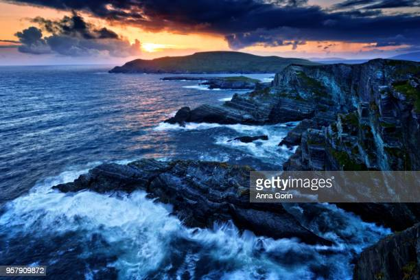 sunset over kerry cliffs along skellig ring with choppy waves forming misty patterns, long exposure - ring of kerry stock photos and pictures
