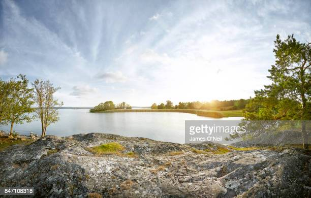 sunset over lake and foreground rocky plateau - meer stockfoto's en -beelden