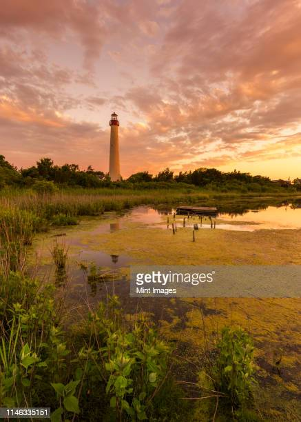 sunset over lighthouse - cape may stock pictures, royalty-free photos & images