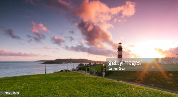 sunset over lighthouse, plymouth, uk - plymouth stock photos and pictures