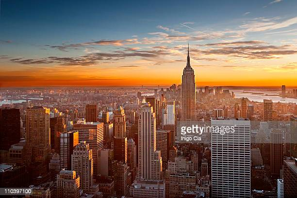 sunset over manhattan - new york skyline stock photos and pictures