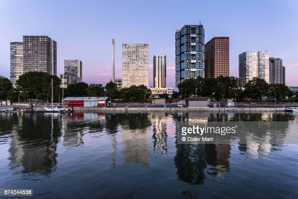 sunset over modern buildings along the seine riverbank in paris - didier marti stock photos and pictures