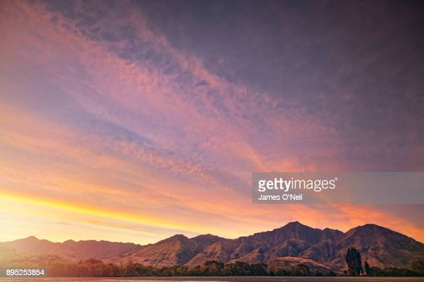 sunset over mountain range with large expanse of sky - moody sky stock pictures, royalty-free photos & images