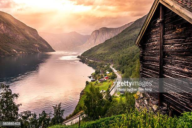 Sunset over mountains and fjord with wooden hut
