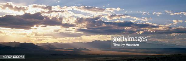 sunset over mountains - timothy hearsum stock photos and pictures