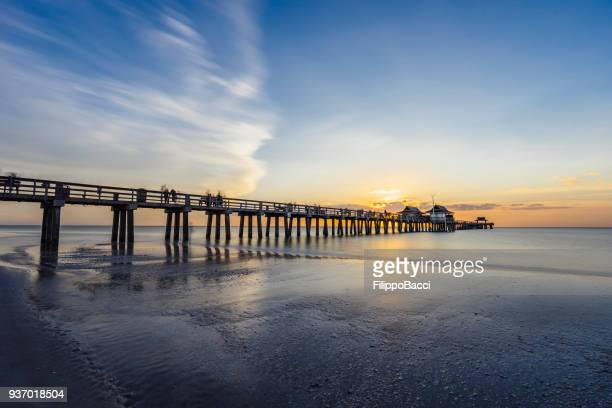 sunset over naples pier in florida from the beach - naples florida stock pictures, royalty-free photos & images