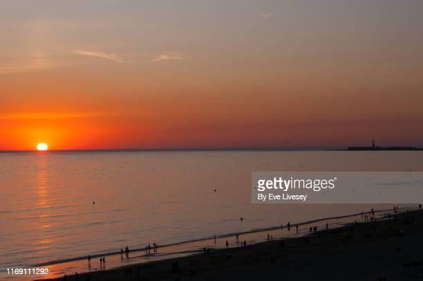 sunset over playa victoria beach - cadiz - ワイドショット ストックフォトと画像