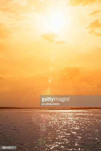 sunset over rippling ocean water - sepiakleurig stockfoto's en -beelden