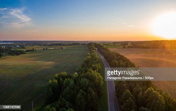 Sunset over road by countryside