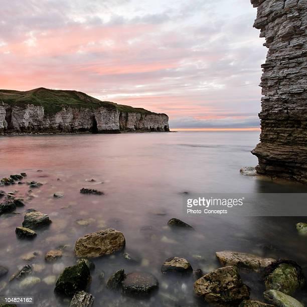 岩の海岸線に沈む夕日 - 炭酸石灰 ストックフォトと画像
