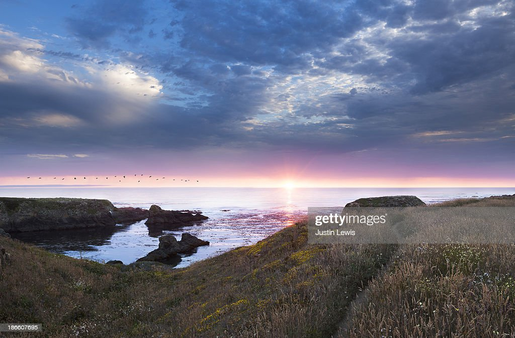 Sunset over rocky ocean coastline with trail : Stock Photo