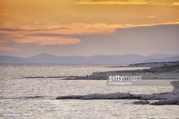 sunset over rocky shores of ovacik with a cloudy sky. - emreturanphoto stock pictures, royalty-free photos & images