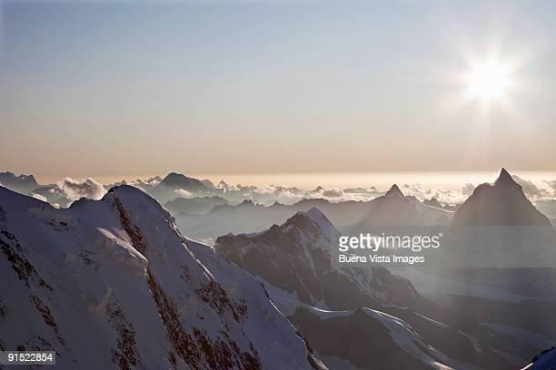 sunset over swiss alps - alpen stock-fotos und bilder