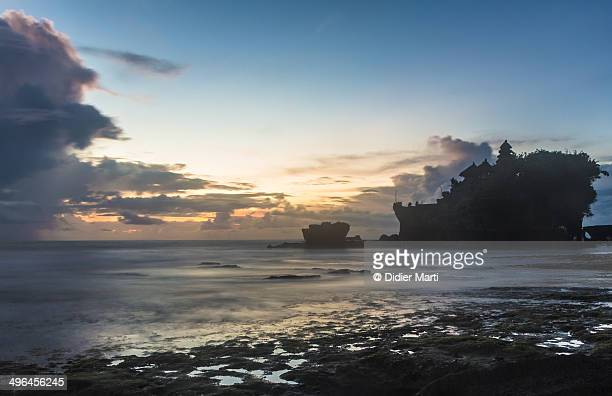 sunset over tanah lot temple in bali - didier marti stock photos and pictures