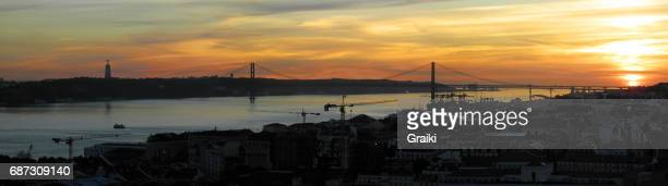 sunset over the '25 of april' bridge in lisbon, portugal. - statua di cristo re foto e immagini stock
