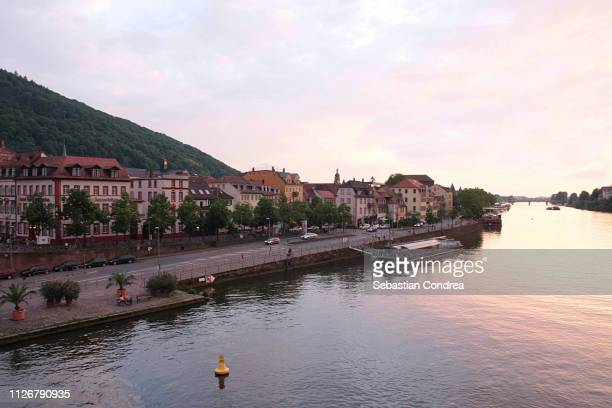 sunset over the beautiful and romantic city heidelberg view from the alte brucke bridge, neckar river, germany - heidelberg germany stock pictures, royalty-free photos & images