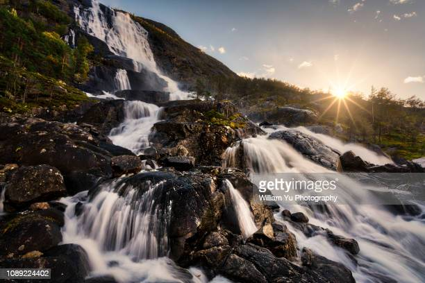 sunset over the beautiful langfoss waterfall - swift river stock photos and pictures