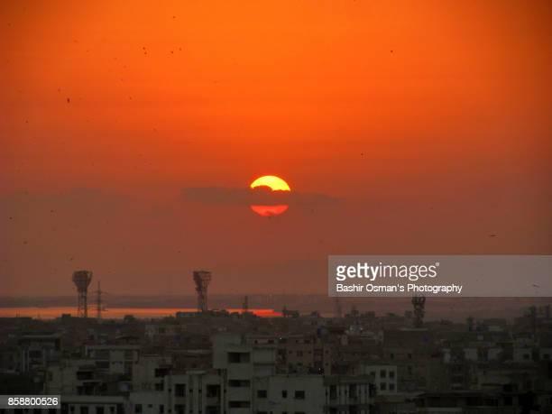 sunset over the city - カラチ ストックフォトと画像