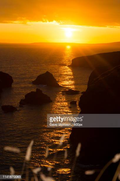 sunset over the coastal rocks with wild highl - david cliff stock pictures, royalty-free photos & images