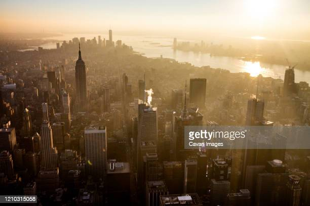 sunset over the empire state building and midtown manhattan, nyc - urban sprawl stock pictures, royalty-free photos & images