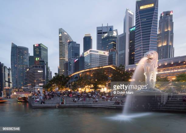 sunset over the famous singapore financial district skyline by the marina bay - didier marti stock photos and pictures