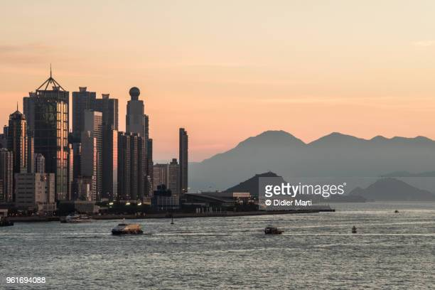 Sunset over the Hong Kong island skyline, the Victoria harbor and the distant peak of Lantau island