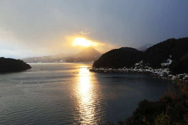 Sunset over the Ine Bay - just after sleety snow falling over the Ine-no-Funaya Houses on cold winter evening ,elevated view
