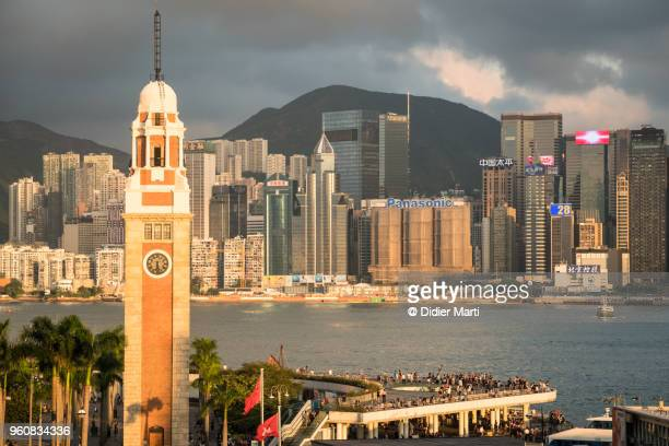 Sunset over the Kowloon clock tower and the Victoria harbor with the Hong Kong island skyline