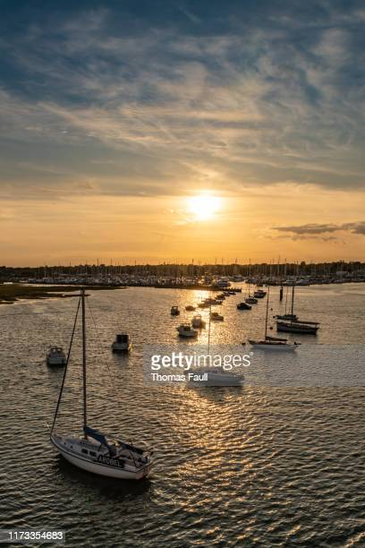 sunset over the marina in lymington with boats moored - lymington stock photos and pictures