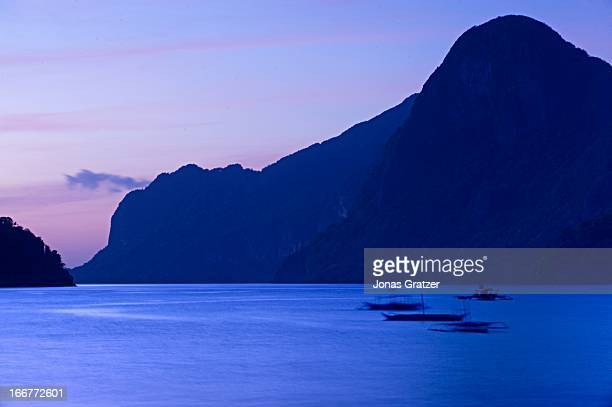 Sunset over the massive rocky limestone which rises from the sea in Palawan archipelago..